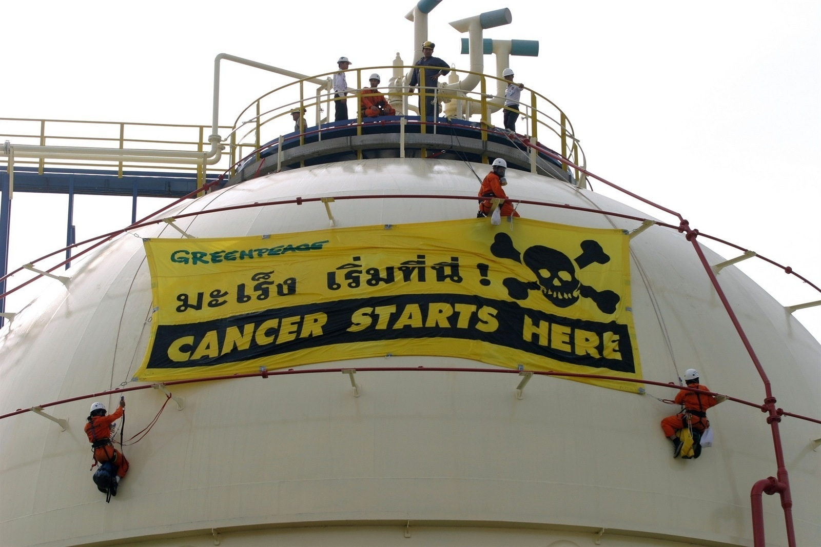 """Activists from the environmental group Greenpeace staging a protest at a processing and storage facility owned by the Thai Plastic and Chemicals Plc (TPC), which contains the highly toxic and carcinogenic chemical Vinyl Chloride Monomer (VCM). The activists climbed onto a storage tank to hang a banner """"Cancer Starts Here"""".   Greenpeace is demanding that TPC's factory operations be shut down after finding evidence that wastewater containing a chemical that can cause cancer and pose threats to the environment are being discharged by the company into the Chao Phraya River."""