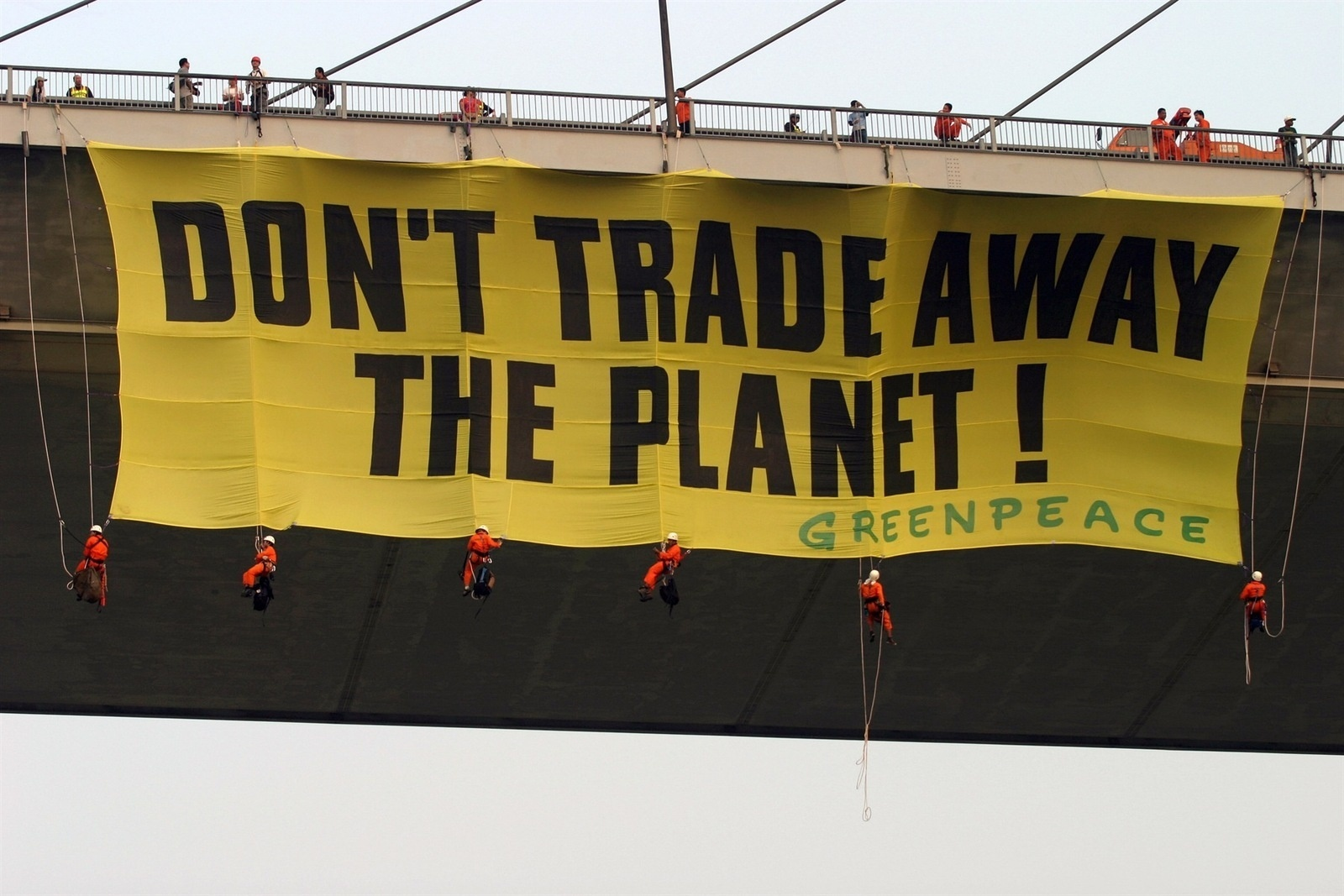 A group of Greenpeace activists hang a huge banner from the Rama IX bridge in the Thai capital Bangkok. About 14 activists took part in the demonstration, including six climbers who abseiled down from the bridge to hang a banner which read 'Don't Trade Away the Planet'. The move was designed to remind delegates at the CITES conference, which closes in Bangkok today, to actively implement and enforce the positive decisions that were taken at the convention. Greenpeace has emphasised the need to end unregulated trade in endangered species. The action was coordinated by Greenpeace's Southeast Asia office. Illegal trafficking in wild animals remains a serious problem in Southeast Asia.