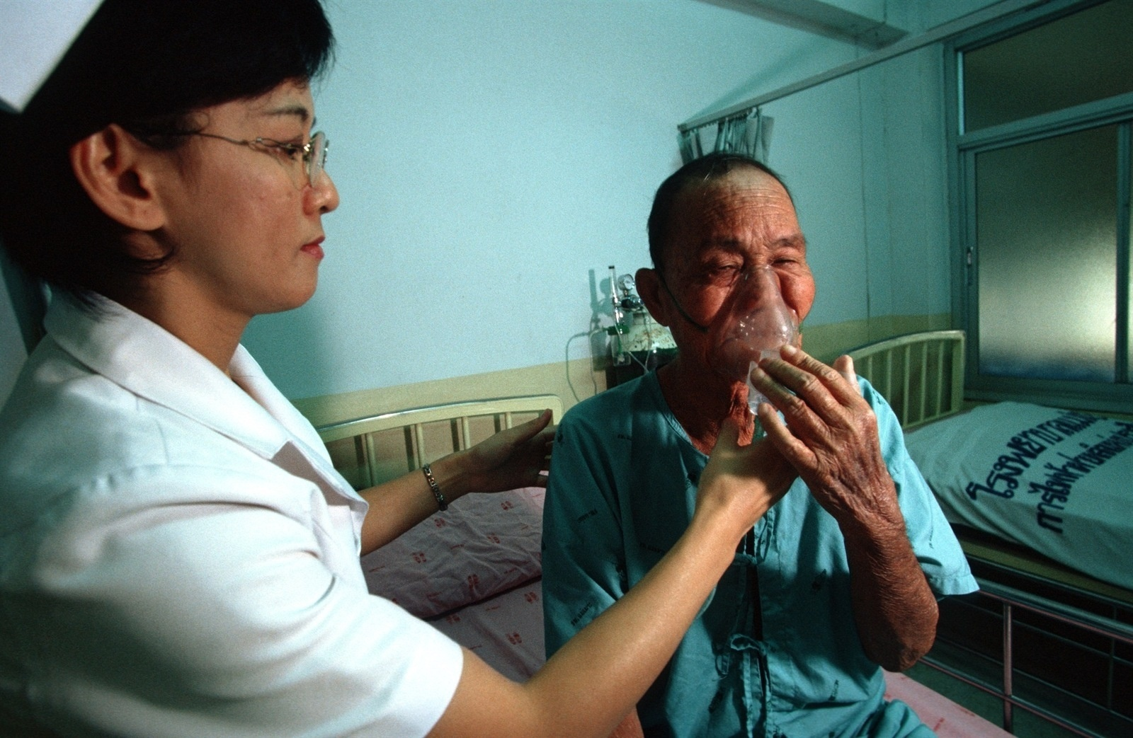 A nurse helps khun Khao Jaiwang, 68, breathe with the help of an oxygen tank at Mae Moh district hospital.  He has been diagnosed with Chronic Obstructive Pulmonary Disease. Environmental activists and villagers in the Mae Moh area believe that emissions from the Mae Moh power plant are the principal cause of respiratory disease in this area. An abnormal number of villagers in vicinity of the power plant are dying of respiratory related illnesses. Mae Moh district in northern Thailand's Lampang province is home to Southeast Asia's largest lignite fired power generating facility. Villagers in the area have long complained that the plant, which supplies north and northeast Thailand with power, is contaminating the surrounding area and poses a hazard to their health as well as damaging agricultural land.  The Mae Moh Power Plant, as it is known, began operations about 30 years ago and, despite being dogged by accusations of excessive pollution and evidence that locals are suffering respiratory problems as a result of burn-off from the plant, has continued to expand production.  Environmental activists in Thailand and elsewhere see the plant as an example of unclean power technology that should not be repeated in other countries. Proponents of coal and lignite plants say it offers cost effective energy with relatively little impact on the environment.