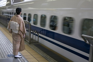 A woman wearing a kimono watches a bullet train pulls into Kyoto central station.