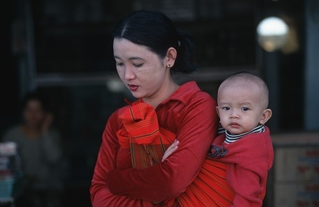 A mother stands with her child strapped to her back in the Burmese border town with China.  China has a growing influence in Burma mostly due to the fact that it is one of the few countries that will still trade with the Military Junta that rules this impoverished nation.