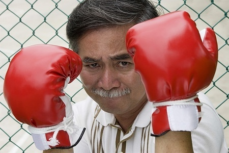 An Asian man trains with boxing gloves.  MODEL RELEASED