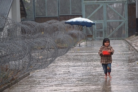 """On a cold and rainy afternoon, a young girl walks past coils of barbed-wire. She is one of the """"Boat People"""" being held at the Lo Wu Detention Center in Hong Kong. Having made the treacherous journey in a rickety boat out of Vietnam, she now faces the prospect of forced repatriation."""