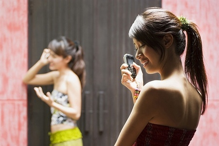 A young Asian girl smiles as she holds her phone while another woman talks on her phone in the background.   MODEL RELEASED